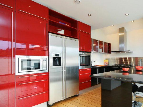 Big Metal Refigerator in Red Kitchen Cabinets facing Black Countertop On Wooden Floor 1024x768