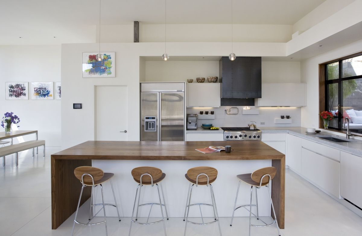 artistic wooden bar stools on the large countertop of large modern apartment kicthen decoration