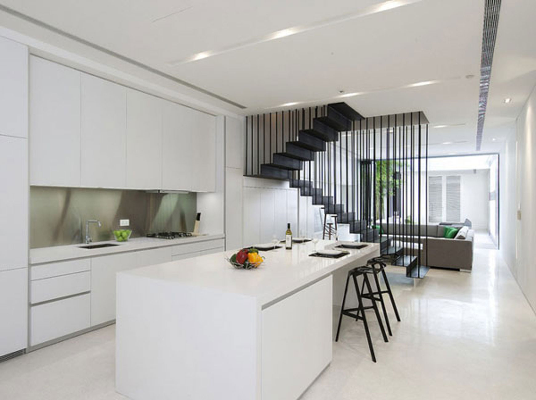 minimalist design of apartment kicthen set with black modern bar stools beside the living room space